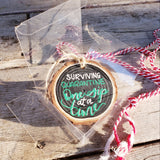 rustic wood slice ornament that says surviving quarantine one sip at at time in green and white hand lettering hanging in a tree in a clear gift box with red and white string