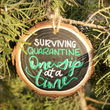 rustic wood slice ornament that says surviving quarantine one sip at at time in green and white hand lettering hanging in a tree