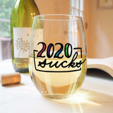 Stemless wine glass with white wine that says 2020 sucks in colorful hand lettering with cork and book