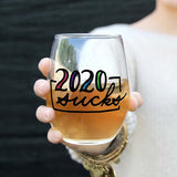 Stemless wine glass with white wine that says 2020 sucks in colorful hand lettering held by woman with bracelet