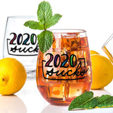Stemless wine glass with iced tea that says 2020 sucks in colorful hand lettering  with lemons and mint