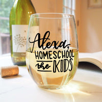 stemless wine glass filled with white wine that says Alexa home school the kids in black hand lettering with cork and book
