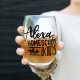 stemless wine glass filled with white wine that says Alexa home school the kids in black hand lettering with woman holding glass