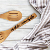 Bamboo wooden slotted spoon wood burned hand lettering that says Bakers Gonna Bake laying on a table with a towel