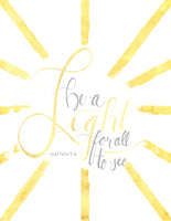 Wall art that says be a light for all to see in golden yellow and grey with golden yellow sun bursts