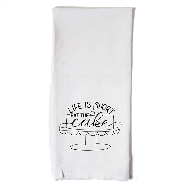 Hand lettered floursack kitchen towel in white that says life is short eat the cake with an illustrated cake on a cake stand with a cherry on top in black