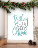 Wall art that says Baby it's cold outside in light blue color and very light blue snowflakes