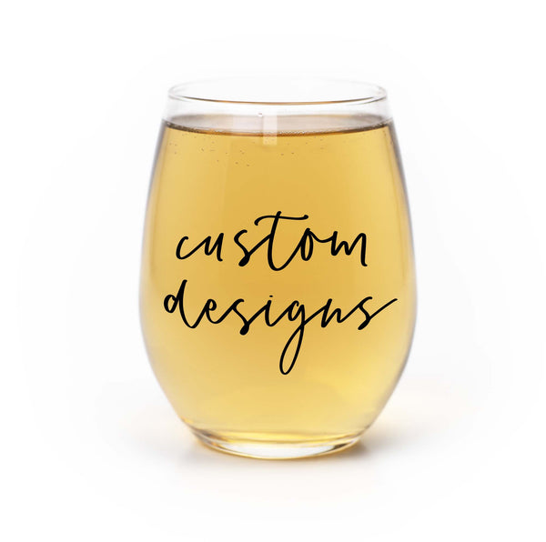 stemless wine glass filled with white wine that says custom designs  in black hand lettering