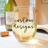 stemless wine glass filled with white wine that says custom designs in black hand lettering with cork and book