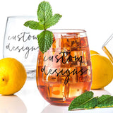 stemless wine glass filled with iced tea that says custom designs in black hand lettering with lemons and mint