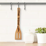 Bamboo slotted kitchen spatula hand lettered and burned with the word gather and a delicate leaf pattern shown hanging in a kitchen next to a canister and potted plant