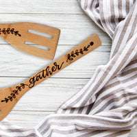 Bamboo slotted kitchen spatula hand lettered and burned with the word gather and a delicate leaf pattern laying on a table with a towel