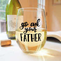 stemless wine glass filled with white wine that says go ask your father in black hand lettering with cork and book