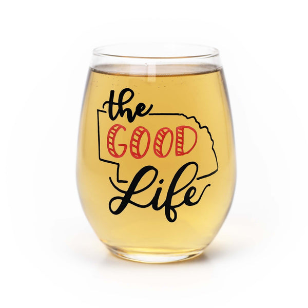 stemless wine glass filled with white wine that says the good life with the outline of the state of Nebraska in red and black hand lettering