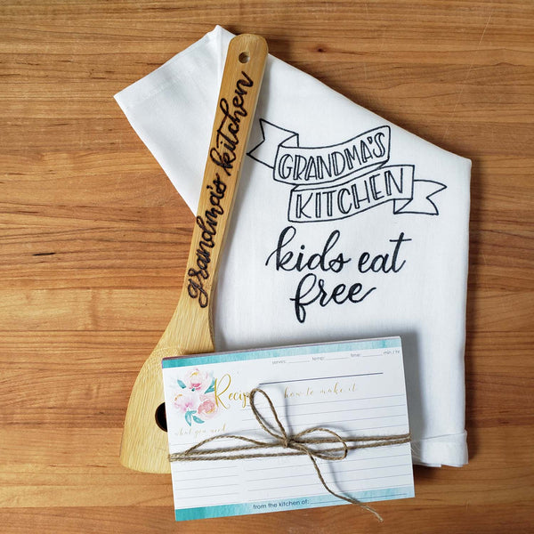 Mother's day kitchen gift set bundle with  floursack towel that says Grandmas Kitchen Kids Eat Free, hand burned bamboo spatula that says Grandma's Kitchen and a set of 12 recipe cards with watercolor florals.