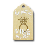 hand painted wooden gift tag that says he put a ring on it with a drawing of a diamond ring in gold and white