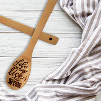 Bamboo round kitchen spoon that says life is short lick the spoon in burned hand lettering laying on a table with a towel