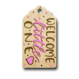 hand painted wooden gift tag that says welcome little one in pink and gold