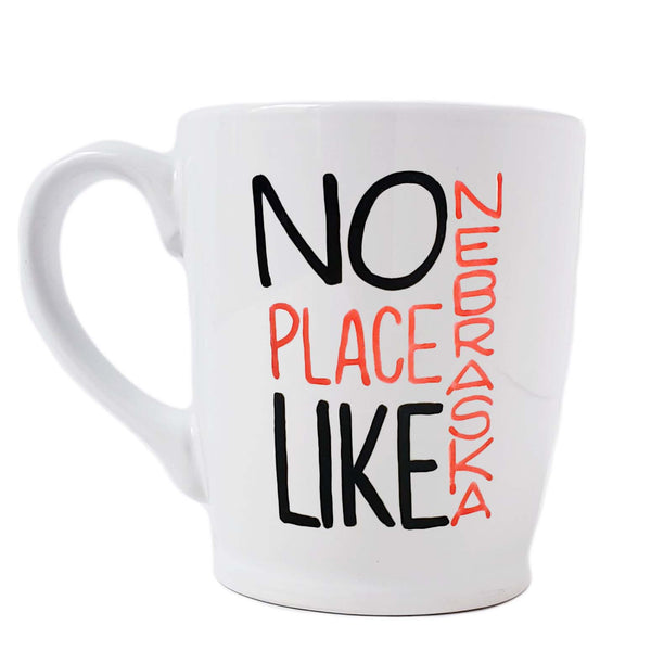 16 oz hand painted white ceramic coffee mug that says no place like Nebraska in red and black hand lettering