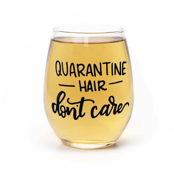 stemless wine glass filled with white wine that says quarantine hair don't care in black hand lettering