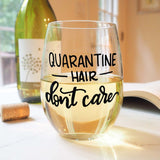 stemless wine glass filled with white wine that says quarantine hair don't care in black hand lettering with cork and book