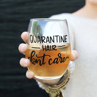 stemless wine glass filled with white wine that says quarantine hair don't care in black hand lettering with woman holding glass