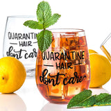 stemless wine glass filled with iced tea that says quarantine hair don't care in black hand lettering with lemons and mint