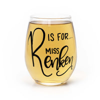 personalized stemless wine glass filled with white wine that says R is for Miss Renken in black hand lettering