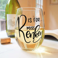 personalized stemless wine glass filled with white wine that says R is for Miss Renken in black hand lettering with cork and book