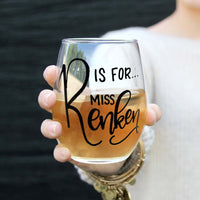 personalized stemless wine glass filled with white wine that says R is for Miss Renken in black hand lettering with woman holding glass