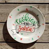 round white plate with red and green star bursts and dots and says cookies for santa in hand lettering with and illustrated banner in black