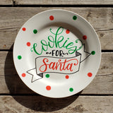 round white plate with red and green polka dots and says cookies for santa in hand lettering with and illustrated banner in black