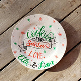 round white plate with red and green star bursts and dots and says cookies for santa love children's names in hand lettering with and illustrated banner in black