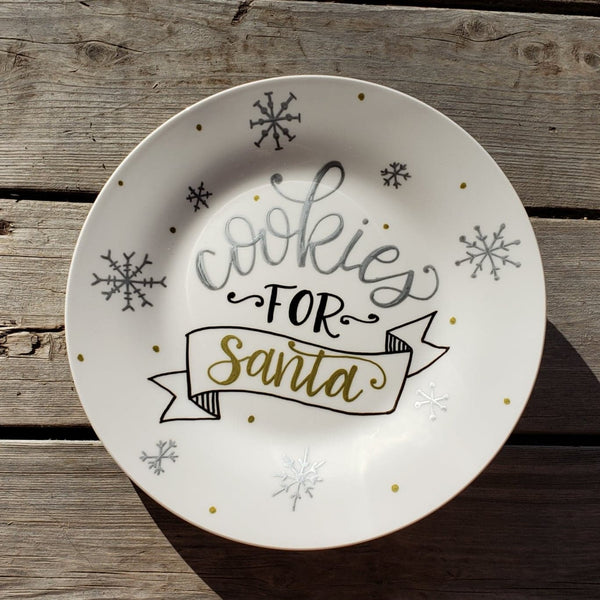 round white plate with gold and silver metallic snowflakes and says cookies for santa in hand lettering with and illustrated banner in black