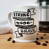 16 oz white ceramic coffee mug that says strong wise brave in black hand lettering with an illustrated ribbon banner