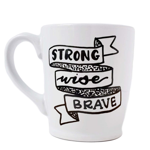 16 oz hand painted white ceramic coffee mug that says Strong Wise Brave with an illustrated ribbon banner in black hand lettering