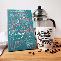 Mother's Day gift set including a hand painted mother's day journal and a hand painted mug that says Strong Wise Brave in an illustrated banner shown with scattered coffee beans and a french press and tea towel in the background