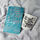 Mother's Day gift set including a hand painted mother's day journal and a hand painted mug that says Strong Wise Brave in an illustrated banner shown nestled in a cozy grey blanket
