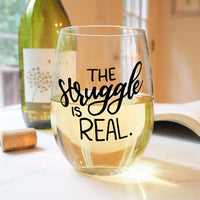 stemless wine glass filled with white wine that says the struggle is real in black hand lettering with cork and book