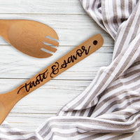 Bamboo round serving fork that says taste & savor in burned hand lettering laying on a table with a towel