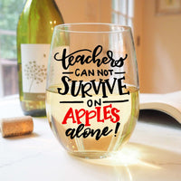 stemless wine glass filled with white wine that says teachers can not survive on apples alone in red and black hand lettering with cork and book