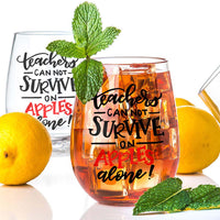 stemless wine glass filled with iced tea that says teachers can not survive on apples alone in red and black hand lettering with lemons and mint