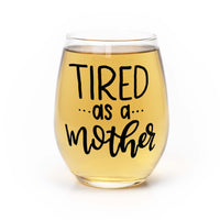 stemless wine glass filled with white wine that says tired as a mother in black hand lettering