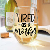 stemless wine glass filled with white wine that says tired as a mother in black hand lettering with cork and book