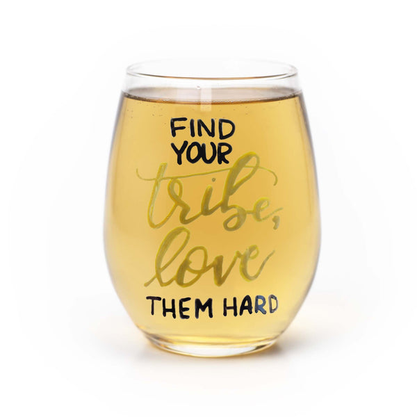 stemless wine glass filled with white wine that says find your tribe, love them hard in gold and black hand lettering