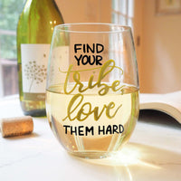 stemless wine glass filled with white wine that says find your tribe, love them hard in gold and black hand lettering with cork and book