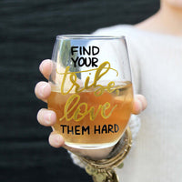 stemless wine glass filled with white wine that says find your tribe, love them hard in gold and black hand lettering with woman holding glass