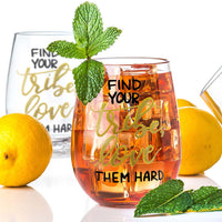 stemless wine glass filled with iced tea that says find your tribe, love them hard in gold and black hand lettering with lemons and mint