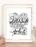 hand lettered wall art design in black and white that says all of us are different none of us are less with an illustration of a heart and winding ribbon shown in a rustic frame on a shelf with accessories