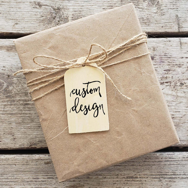 Brown kraft paper wrapped box with twine and wooden gift tag that says custom design
